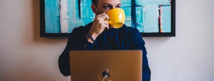 A person sipping coffee while doing remote work from home