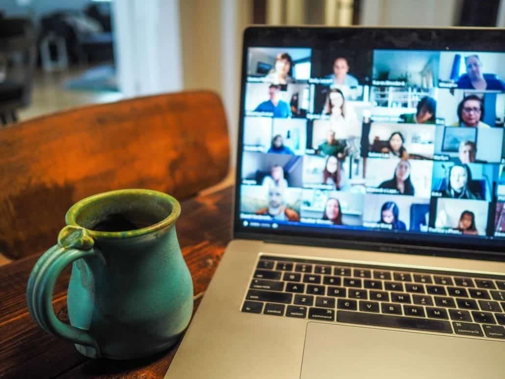 a coffee mug in front of a computer during a virtual meeting